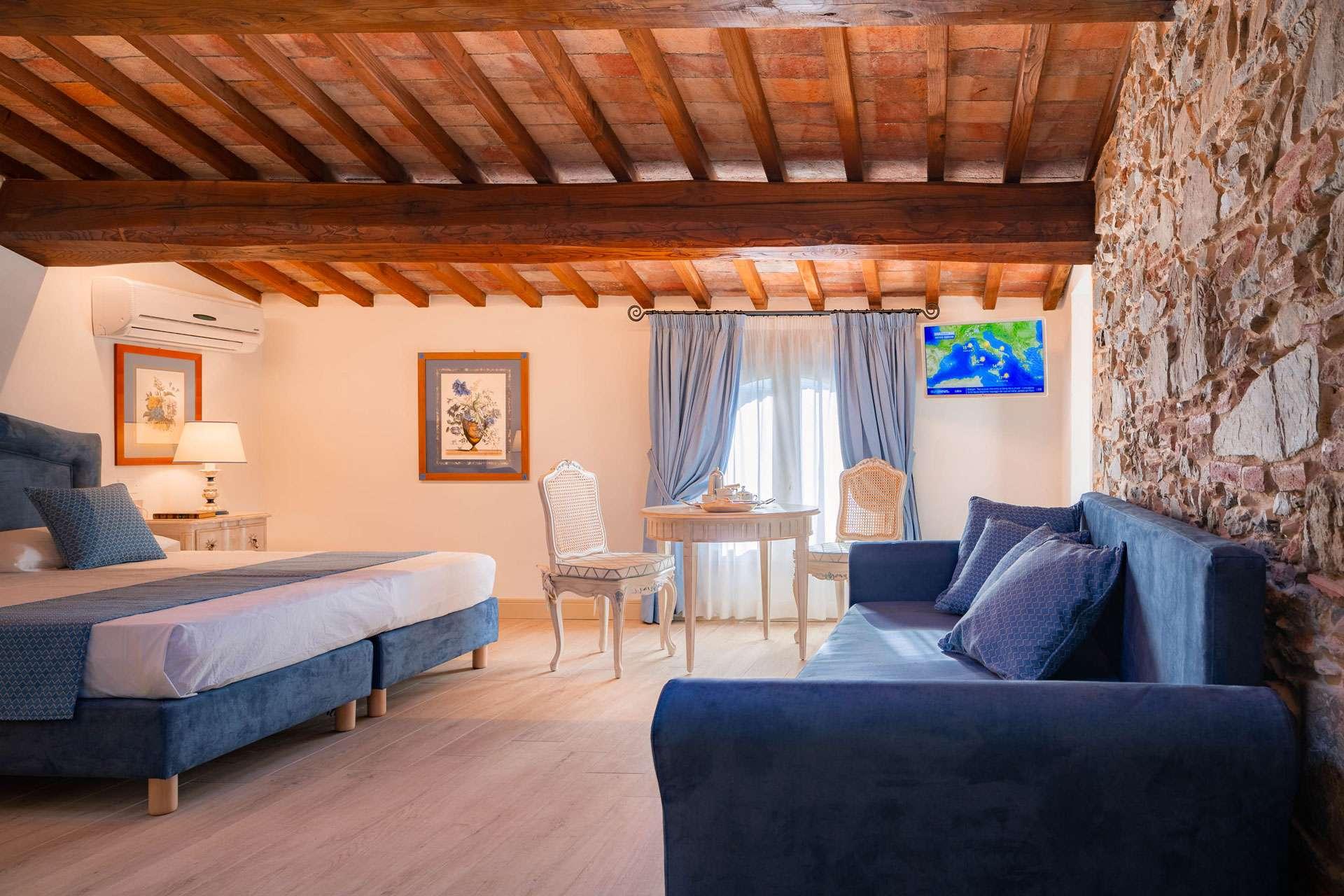 camera sui toni dell'azzurro con letto e divano letto e travi in lego tipiche della campagna di Firenze