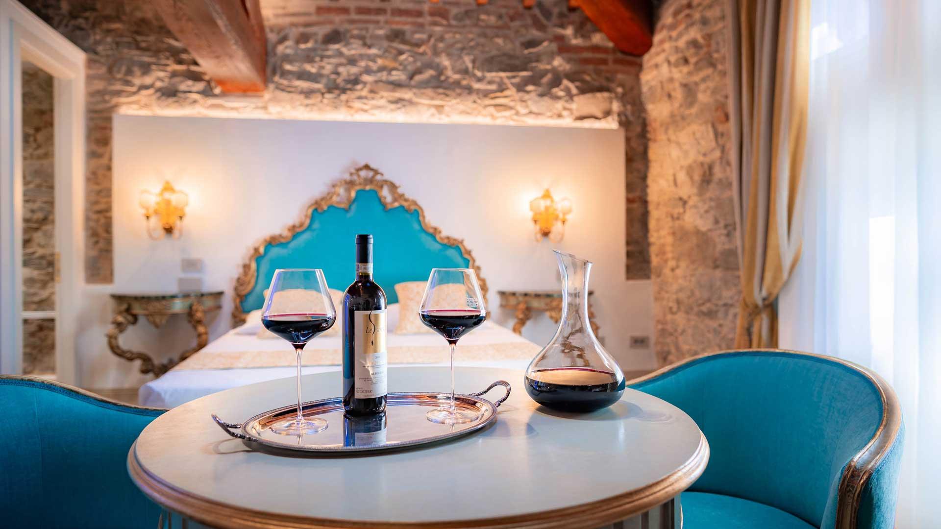 Una delle camere dell'agriturismo vicino a Firenze, primo piano di una bottiglia di vino e decanter