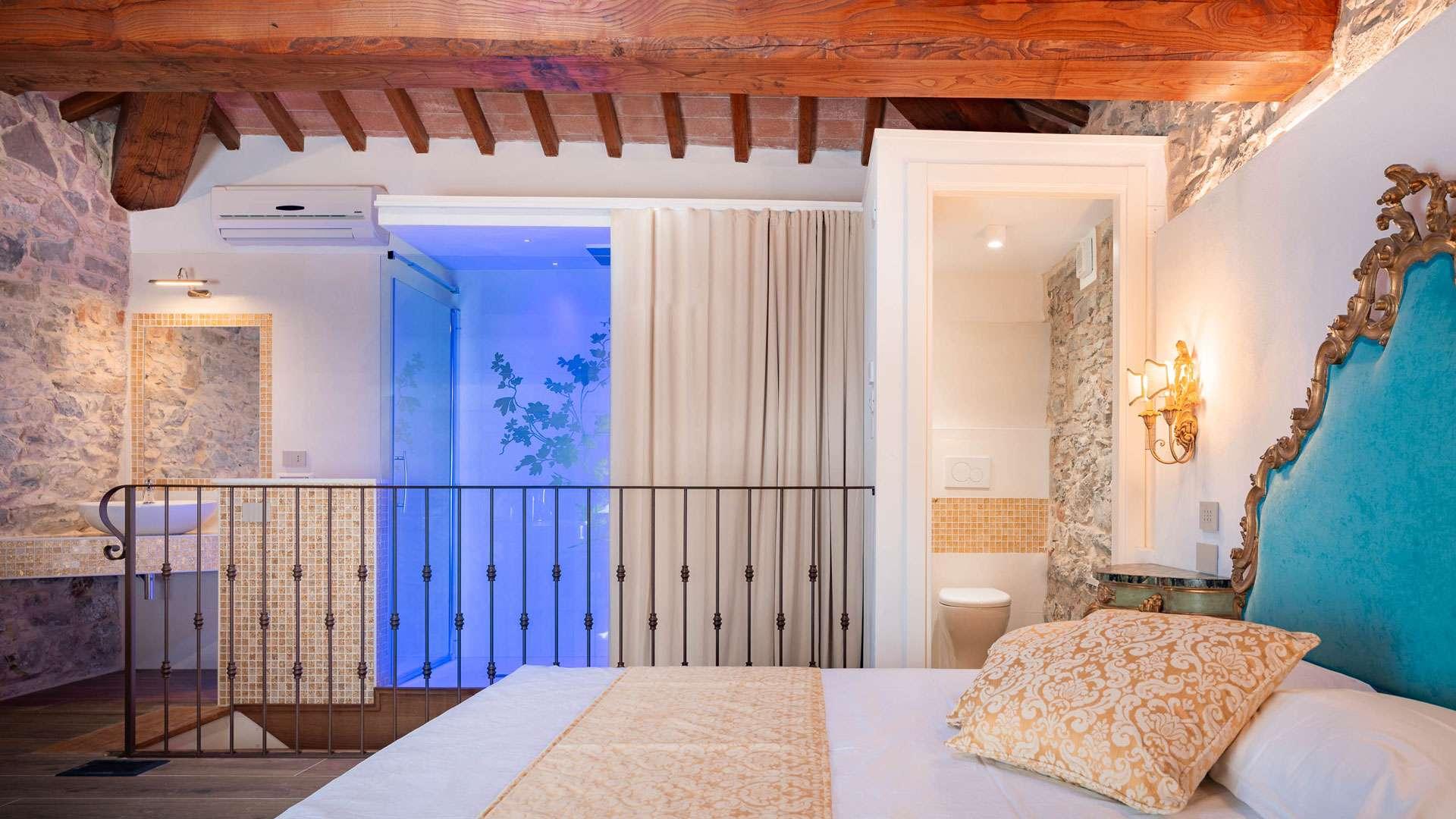 Una delle camere dell'agriturismo, con travi in legno e pareti in pietra a vista