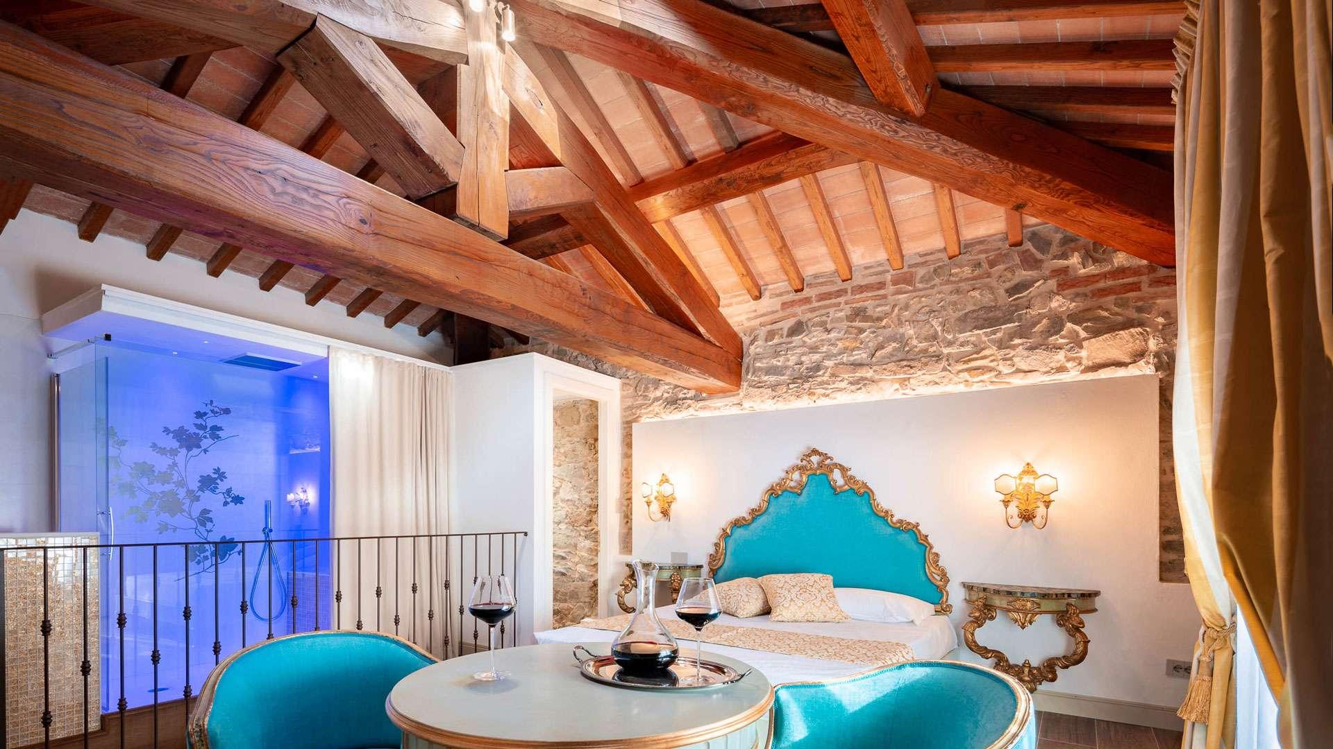 Una delle camere di lusso in campagna vicino a Firenze, con travi in legno e pareti in pietra a vista