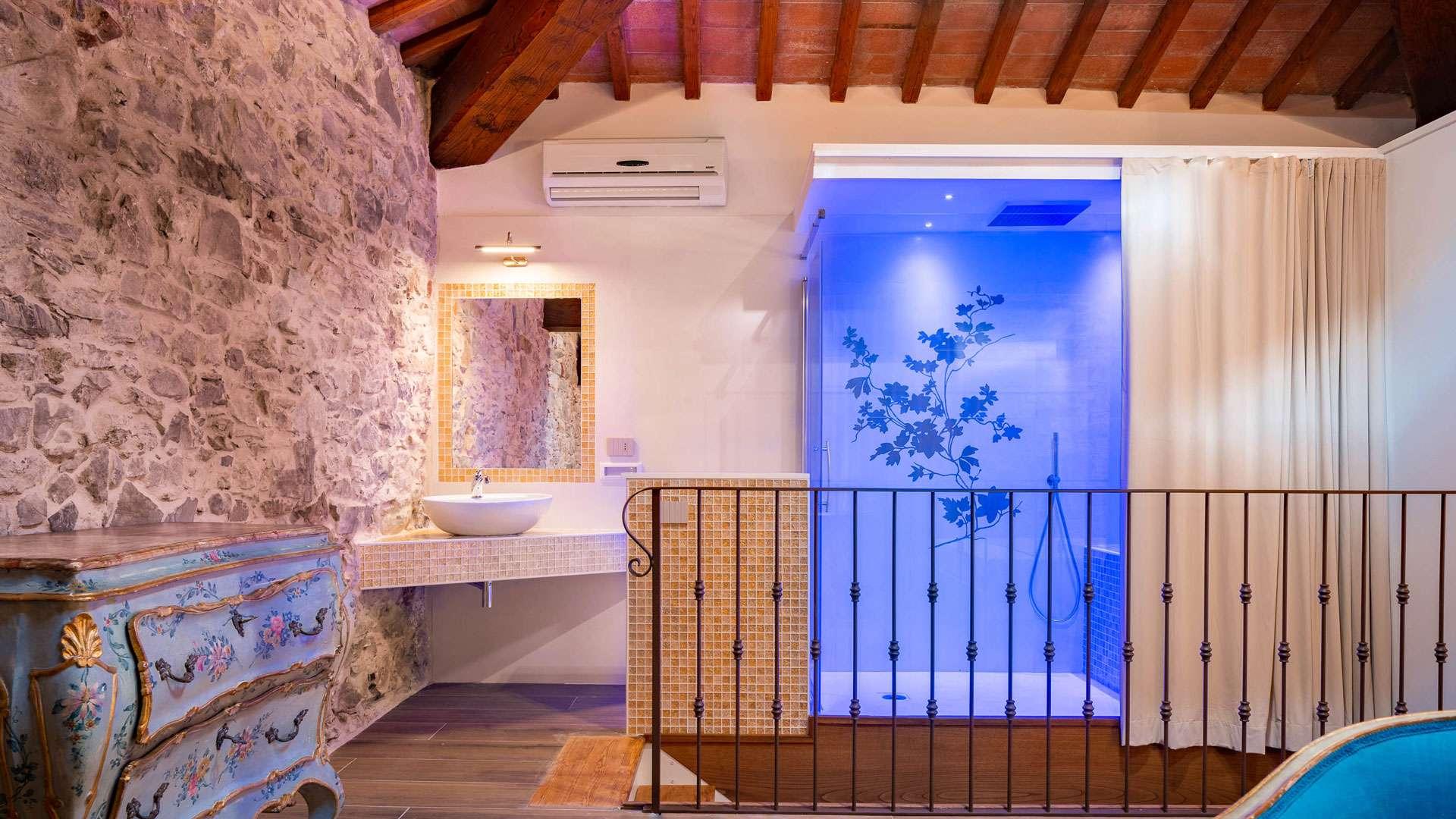 Una delle camere di lusso in campagna vicino a Firenze, con ampio box doccia a vista in camera