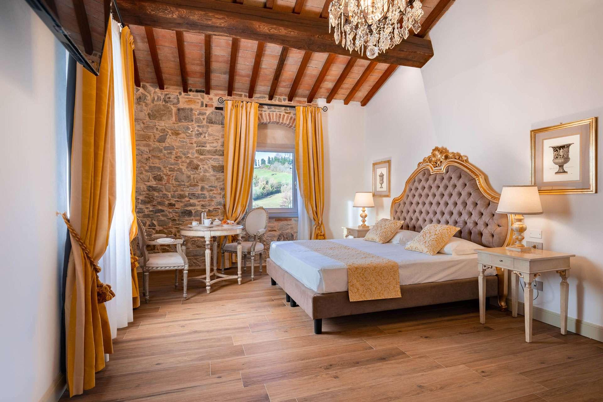 Con muri in pietra a vista e travi in legno questa è una delle più belle Camere in agriturismo vicino a Firenze