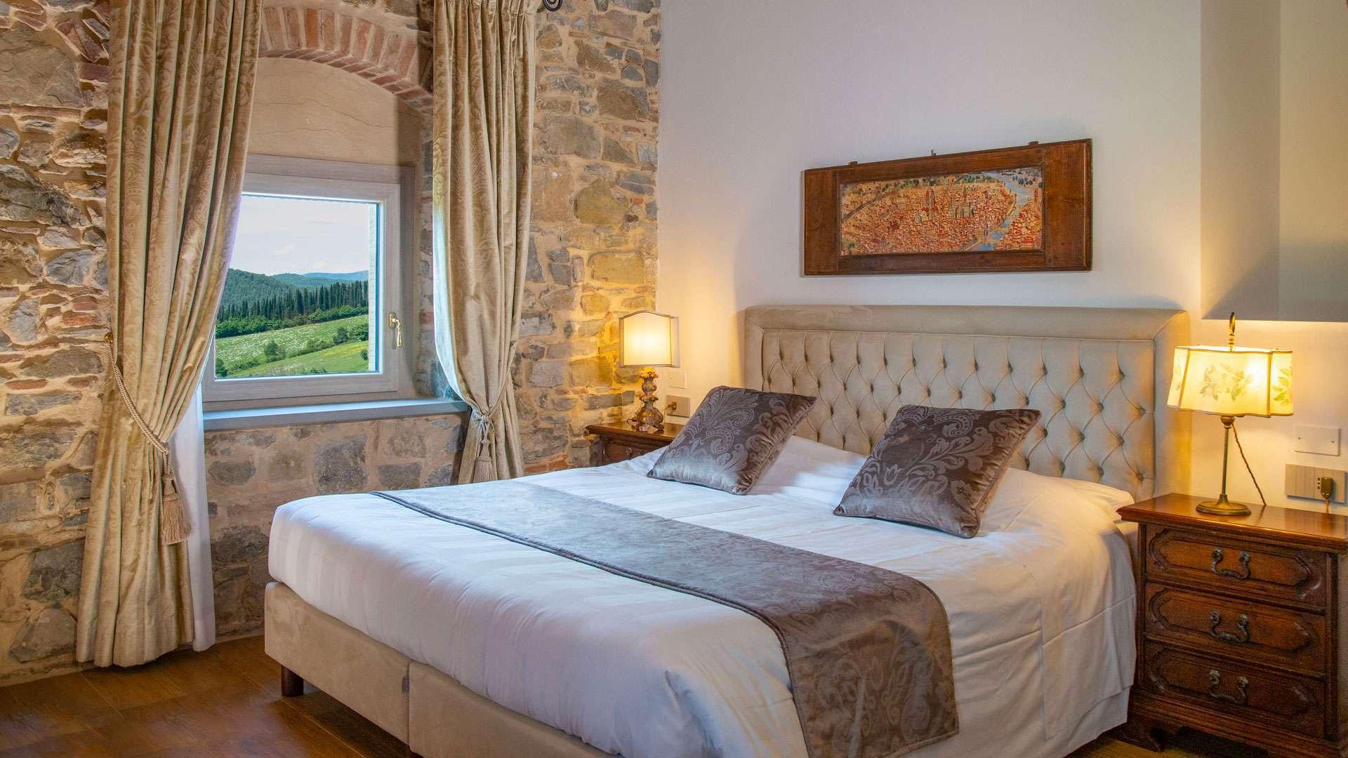Camera con vista in Mugello, dalle finestre si ammira la tenuta mentre l'interno della camera ha un fascino d'altri tempi, con muri in pietra e arredo antico