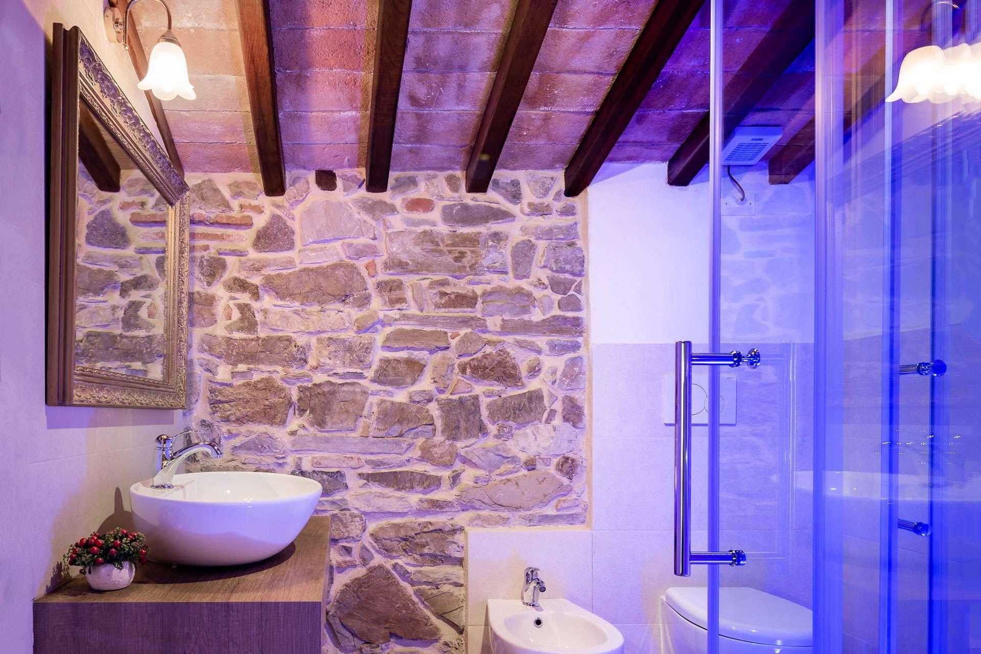 bagno della camera turchese, con muri in pietra e cromoterapia